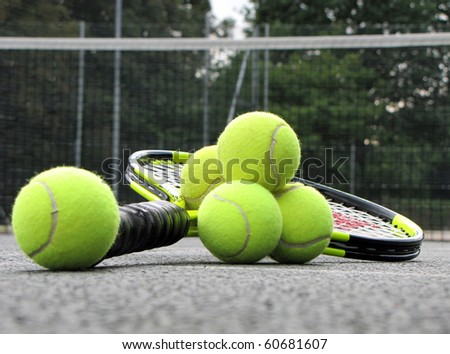 Tennis equipment on the court , Tennis balls and racket left on the court