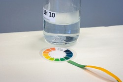 Test strip with litmus paper color chart for determining the acidity of a liquid