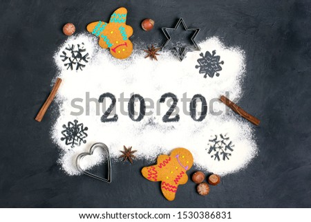 2020 text made with flour with decorations on a black background. Flat lay. Merry Christmas, happy New year concept. Ingredients for making gingerbread - flour, sugar, eggs, cinnamon, cloves, nuts.