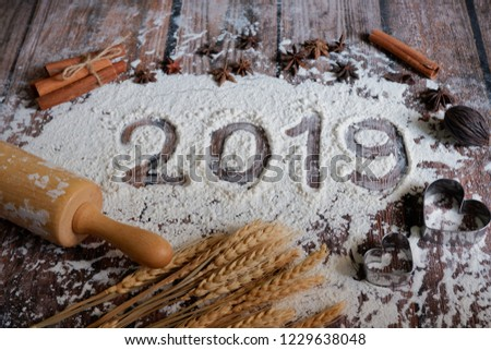 2019 text made with flour with decorations on a wooden background.