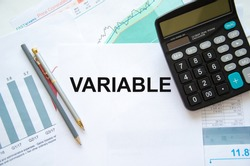 text The variable is written in a notepad. Variable universal life insurance. the text is written on a white piece of paper. in the lens of a calculator and pens. High quality photo