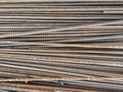 texture closeup : steel rebar for reinforcement concrete at construction site with house under construction background