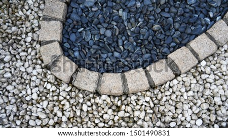 texture of white and dark sea pebbles. strip of pebbles. yin and yang