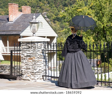 19th Century lady with parasol overlooking period houses in old town