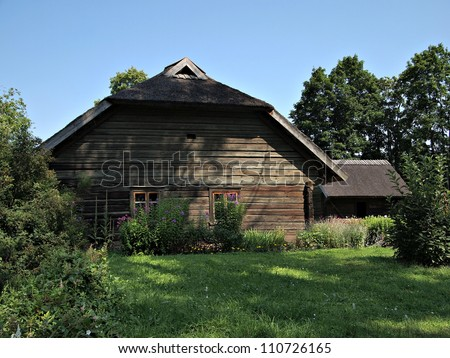 19th century Latvian village traditionally wooden building with a thatched roof