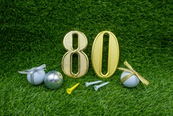 80th golf ball and tee are on green grass