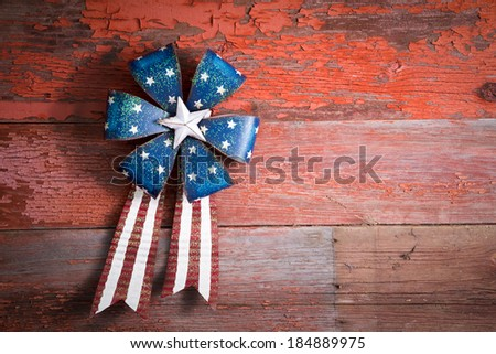 4th July patriotic badge in the form of a circular rosette with blue stars and a ribbon with the red and white stripes of the national flag on rustic wood