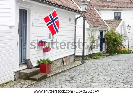 17th May Norway celebrates its constitution day. Is is a very happy day when national flags are waved and parades take place. Here a quiet corner of gamle Stavanger (cruise ship in the background)