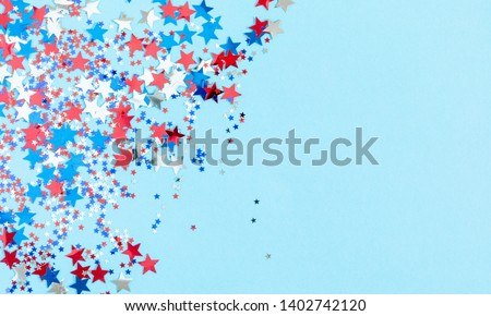 4th of July American Independence Day. Red, blue and white star confetti decorations on blue background. Flat lay, top view, copy space #1402742120