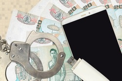 20 Thai Baht bills and smartphone with police handcuffs. Concept of hackers phishing attacks, illegal scam or online spyware soft distribution