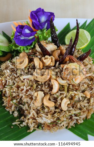 Thai fried rice with shrimp and herb decorated by purple flowers - stock photo