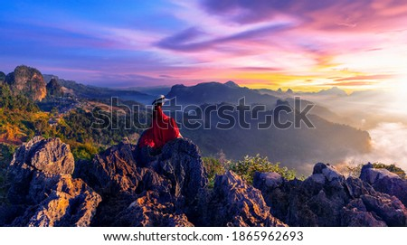 Thai girl wearing a red dress sits on a rock at Ban Jabo viewpoint, Mae Hong Son Province, Thailand Zdjęcia stock ©