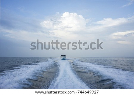 THAILAND - JANUARY 3, 2014: A white motor boat rushes through the blue sea, leaving a trail. Tourists sail from the island to the island by boat, as part of an ordinary excursion, in Thailand. #744649927