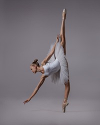 The ballerina in the twine stretches to the floor. Photo in color.
