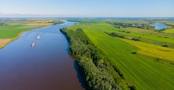 The barge goes along the river with a cargo in the background of fields and forest. Photo from the drone. Two ships.