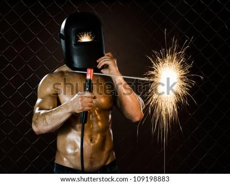 the beauty muscular worker welder man weld electric arc