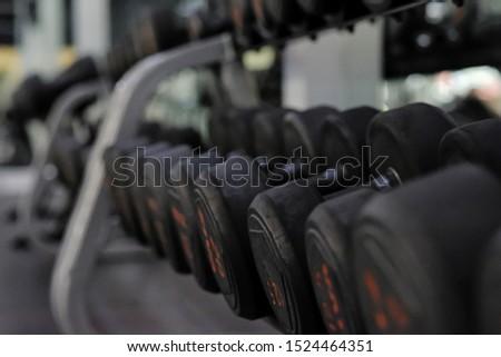 The black dumbbells in a rack ,dumbbells in fitness gym.workout dumbbells.