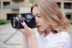 The blonde learns to photograph and earn money on the photo. A girl photographer walks around the city and takes pictures of everything around.