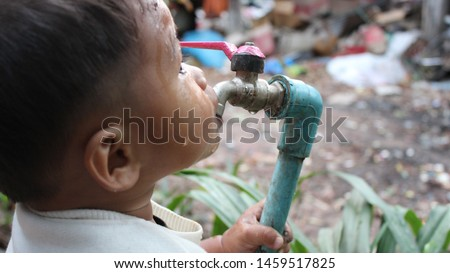 The boy is drinking water with thirst from the dirty water pipe, shooting blurred images Сток-фото ©