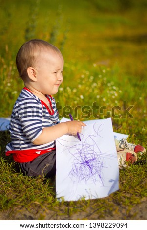 The child draws a drawing with markers