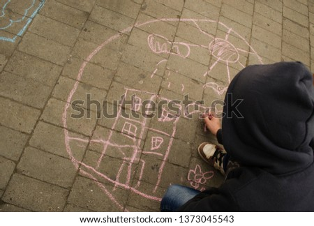 The child draws on the asphalt drawing colored chalk. #1373045543