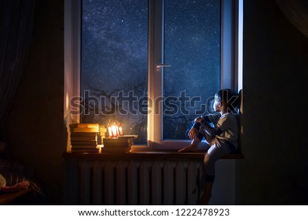 The child sits on the windowsill at night looking at the stars and dreams.