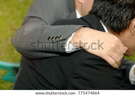 The concept of encouragement for business associates failed : Business associates sit with their arms around their shoulders, comforting their colleagues, sad seats.  #775474864
