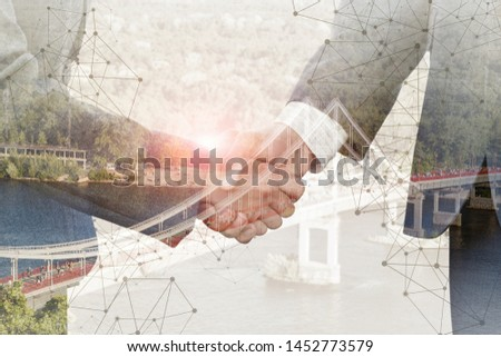. The concept of the agreements reached in the business. Handshake on the background of the bridge #1452773579