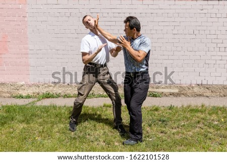 The defender performs a palm strike on the face of the attacker on the street. Martial arts instructors demonstrate self-defense techniques of Krav Maga