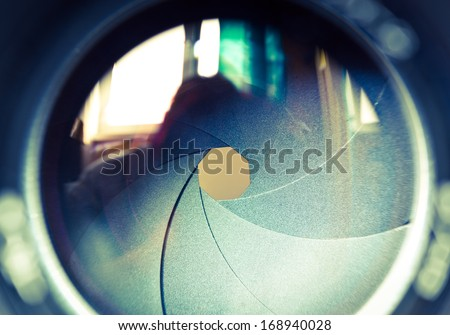 The diaphragm of a camera lens aperture. Selective focus with shallow depth of field. Color toned image.