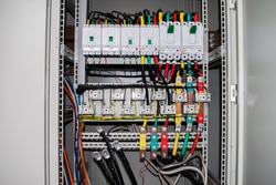 The electrical box contains many terminals, relays, wires and switches
