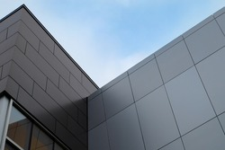The exterior wall of a contemporary commercial style building with aluminum metal composite panels and glass windows. The futuristic building has engineered diagonal cladding steel frame panels.