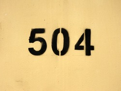 The figure is five hundred and four. Black numbers are drawn on a yellow wall using a stencil.