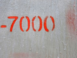 The figure of seven thousand is depicted using a stencil. Red number on a gray wall.