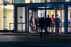 the flow of people passing through the revolving door of the modern office building at the end of the working day