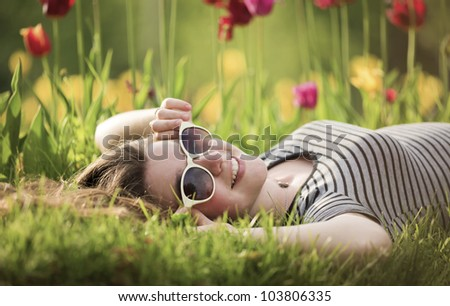 The girl lies on a bed with tulips