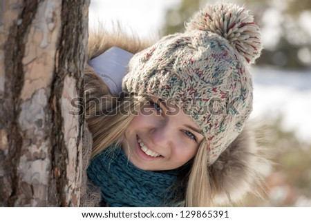 The girl smiles looking out because of a tree trunk