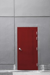 the gray wall with the red door