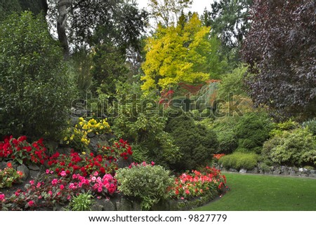 The green lawn surrounded by flower beds and blossoming trees