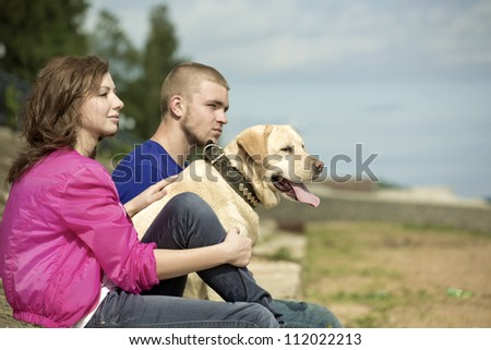 The guy, the girl and dog sit on a beach