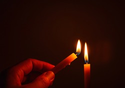 The hand that is lighting candles in the dark With burning candles shining the light at night  Design for the background, Burning candles on black background, Candle in hand, Candles in the dark.