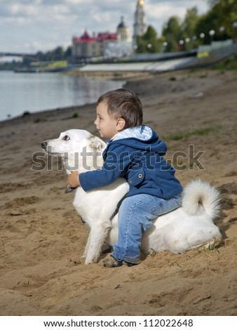 The kid sits on a dog