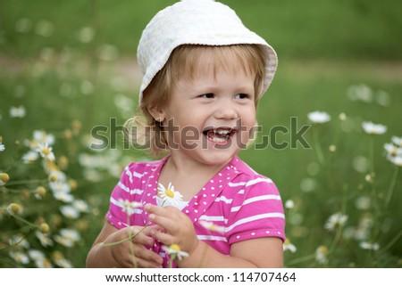 The little girl among camomiles