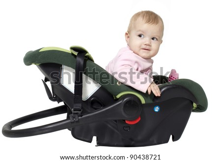 The little girl sits in an automobile cradle