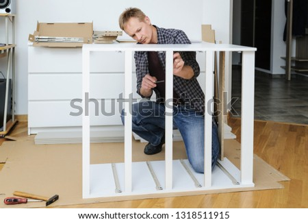 The man is assembling the furniture at home. He is mounting and fastening the frame of the chest of drawers.