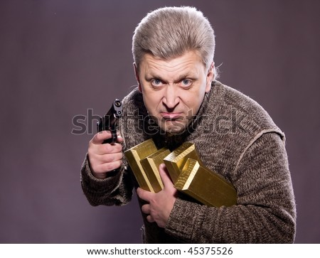 The man robber with a pistol and gold