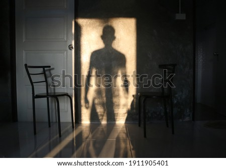 The man's shadow stood in the door on the wall. Сток-фото ©