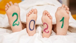 2021, the numbers are painted with bright colors on children's heels, the children are covered with a sheet.