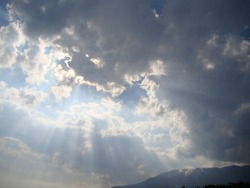 the rays of the sun break gray clouds