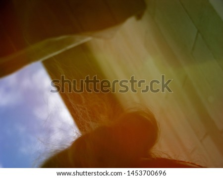 the reflection of the strands of hair on the surface of the water in the background reflected from the sun of heaven next to the mirrored wall #1453700696